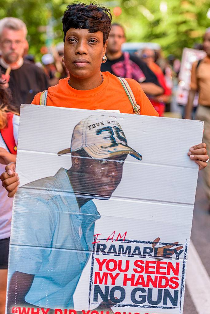 Constance Malcolm, holding a sign with a picture of Ramarley. According to an interview with USA Today, Ramarley loved animals and volunteered at a pet store just to be around them. Photo via Getty/Pacific Press